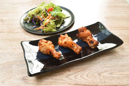 crispy fried chicken drum wing with barbecue sauce and vegetable on plate