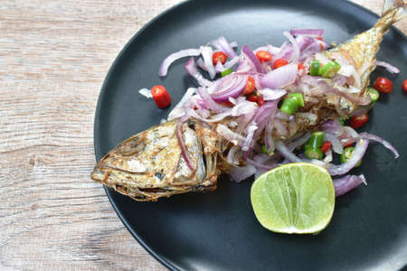 deep fried salty mackerel fish topping chop shallot and chili with slice lemon on plate Imagens