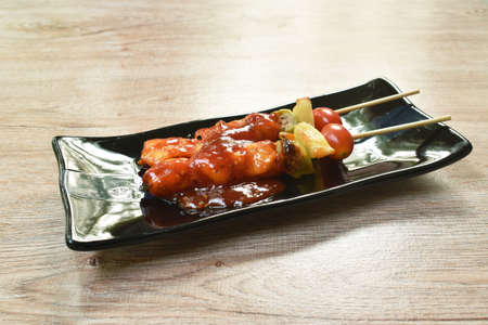 roasted chicken with pineapple chili and tomato dressing barbecue sauce stabbing wooden stick on plate Imagens
