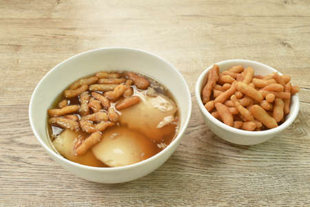 boiled soybean tofu pudding custard in ginger juice soup topping mini crispy fried Chinese dough in bowl on table Imagens