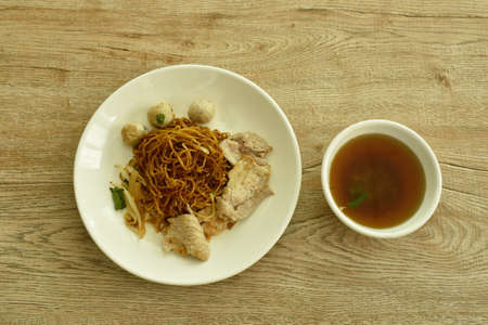 dried Chinese yellow egg noodles topping slice boiled  pork and meatball dressing black sweet soybean sauce on dish with soup Imagens