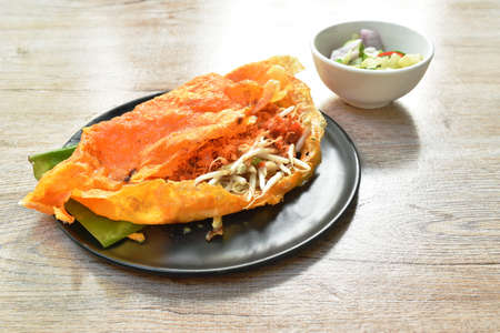 Vietnamese omelette stuffed fried bean sprout and mashed salty shrimp on plate dipping sweet sauce