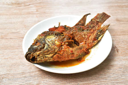 batter fried mango fish dressing spicy and sweet sauce on plate