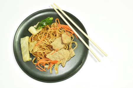 fried yakisoba Japanese noodles slice pork and cabbage with carrot eat by wooden chopsticks on plate