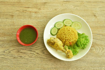 rice cooked with chicken in curry on plate dipping spicy chili sauce Imagens