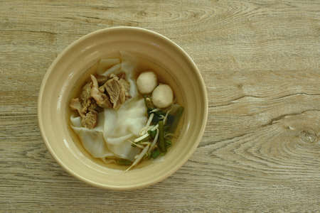 large rice noodles topping slice braised and fermenting with meatball in herb brown soup on bowl Imagens