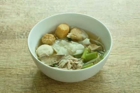 large rice noodles topping slice boiled pork and ball in soup on bowl Imagens