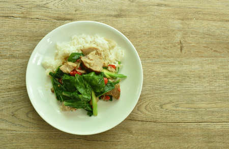 stir fried Chinese kale with slice stew pork leg and chili on plain rice in plate Imagens