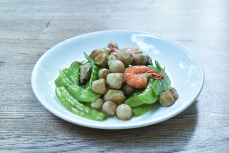 stir fried green pea and straw mushroom with shrimp couple pork in soybean sauce on plate Imagens