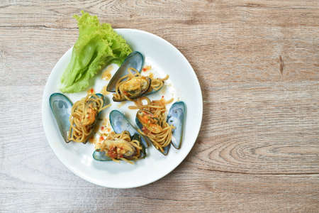fried spicy spaghetti with basil leaf roll topping mussel dressing chili sauce on plate