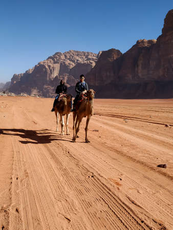 Two men riding camel in the wadi rum desert. Jordan