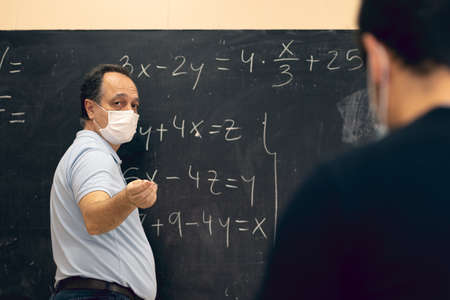 Adult teacher wearing mask explaining mathematical lessons to a student. Covid situation, pandemic, new normal. Banco de Imagens