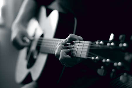 Young man playing acoustic guitar in black and white