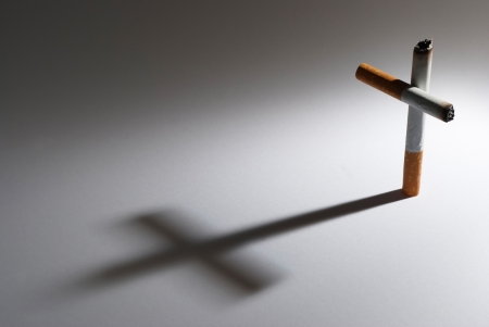 exclusion: A cigarette with it shadow making a cross