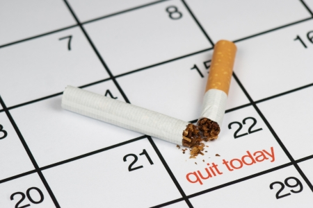 A broken cigarette above a calendar, saying  quit today