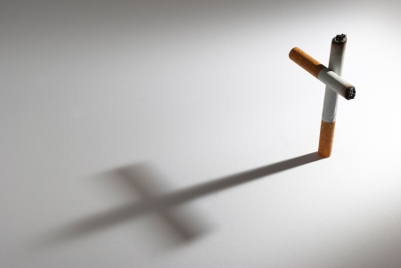 A cigarette with it shadow making a cross photo