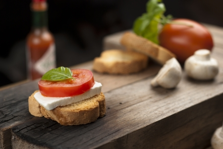 antipasto: wood table with an italian antipasto, with fresh cheese, tomato and basil