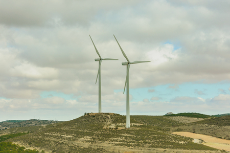 wind turbines in the field against blue cloudy sky, electric generators in countryside, windmills in work Banque d'images