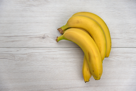 Bananas on white wood table, top view.