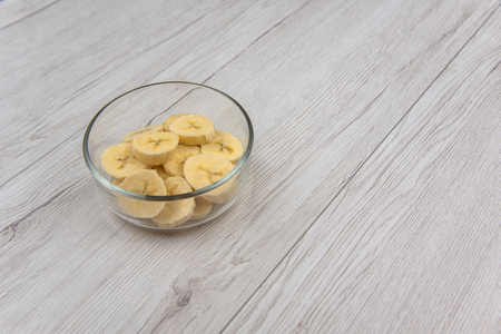 Raw yellow banana fruit slices in a bowl on white wood table Standard-Bild