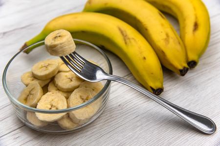 Rohe gelbe Bananenfruchtscheiben in einer Schüssel mit einer Gabel auf weißem Holztisch Standard-Bild