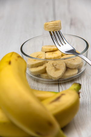 Rohe gelbe Bananenfruchtscheiben in einer Schüssel mit einer Gabel auf weißem Holztisch