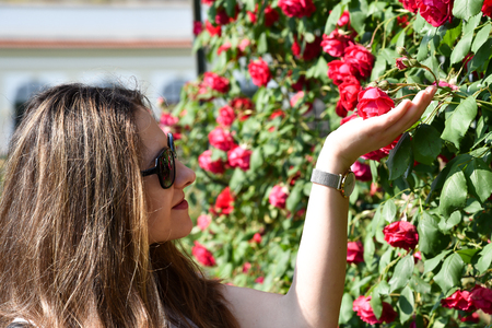 Portret of a young girl admiring roses in the park