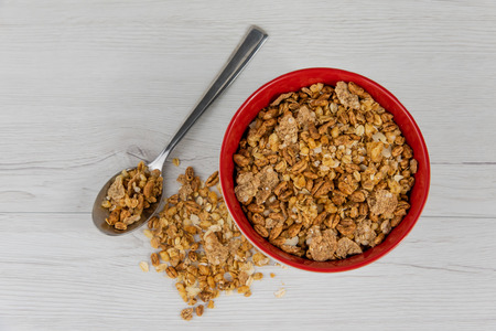 A red bowl on full of granola with a spoon on white wood table, top view
