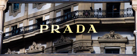Milan, Italy - May 25 2018: Selective focus on Prada shop logo with Galleria Vittorio Emanuele II on background in Milan, Italy
