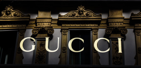Milan, Italy - May 25 2018: Selective focus on Gucci shop logo with Galleria Vittorio Emanuele II on background in Milan, Italy
