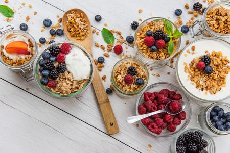 Jars full with granola, yogurt and fresh berries and wood spoon full whit granola, top view, selective focus