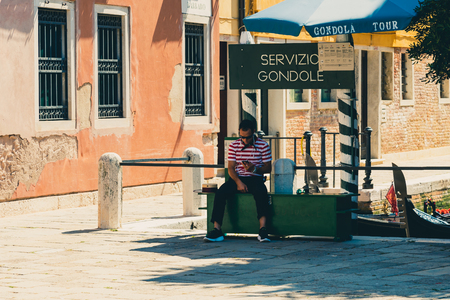 Venice, Italy - August 22 2018: Gondolier waiting for clients for a gondola ride in Venice, Italy.