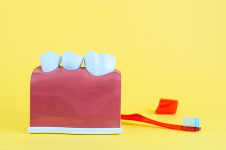 False mouth on yellow background with toothbrush