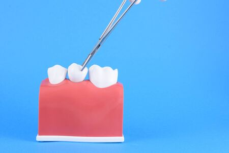 False mouth dentist in blue background with hand working Archivio Fotografico
