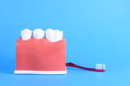 False mouth on blue background with toothbrush