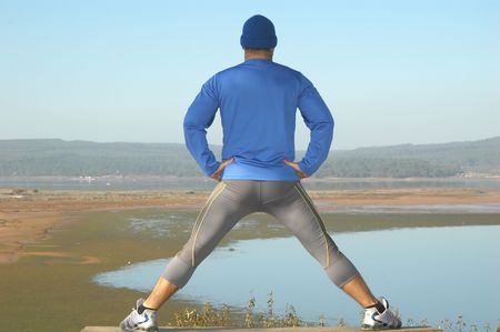Middle age man making stretching movements before run photo