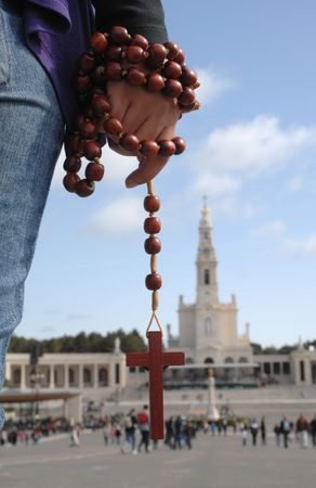 Hands with a crucifix with Fatima (Portugal) temple as background