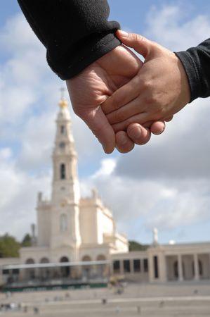 sanctity: Mani con un crocifisso con il tempio di Fatima (Portogallo) come sfondo