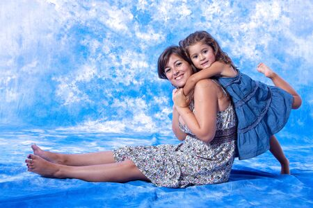 mother and daughter play on studio photo