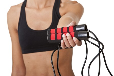 Sports Woman ofering  jumping rope, shallow focus on the roap handles Stock Photo