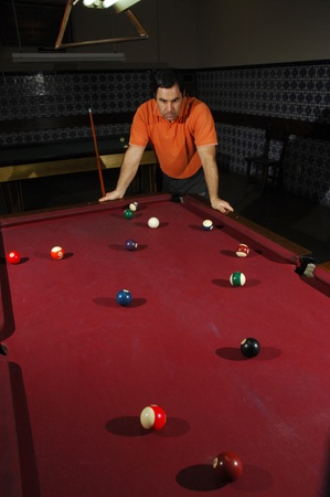 Snooker player taking a long shot across the table photo