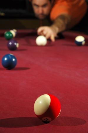 long shot: Giocatore di biliardo che prende un lungo tiro attraverso il tavolo