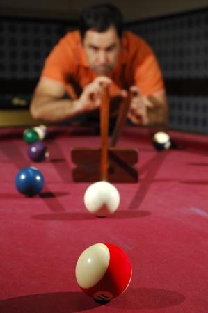 long shot: Giocatore di biliardo che prende un lungo tiro attraverso il tavolo (focus sulla prima palla)