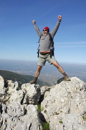 bergbeklimmen: Een knappe middelbare leeftijd latino latin man in de top van een in de bergen wandelen