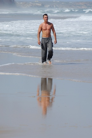 Latino man walking on a quiet beach photo