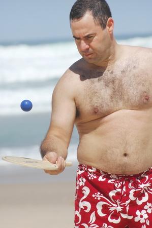a fat man playing beach tennis on the beach