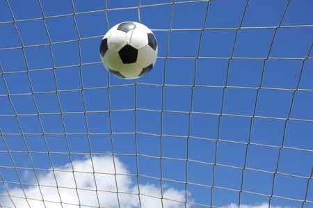 soccer gool, the ball into the net against blue sky