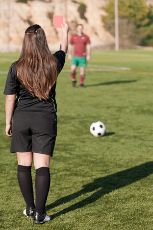 female referee showing the red card to the player photo