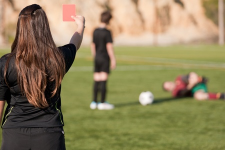 female referee showing the red card to the player with a injured player on the field Stock Photo