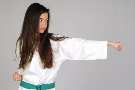 martial artist: girl in Karate moves on grey background